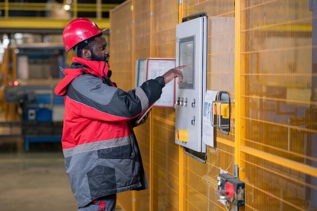 Grave giovane uomo di colore in abbigliamento da lavoro e casco che sceglie le configurazioni sul pannello di controllo nel negozio della fabbrica