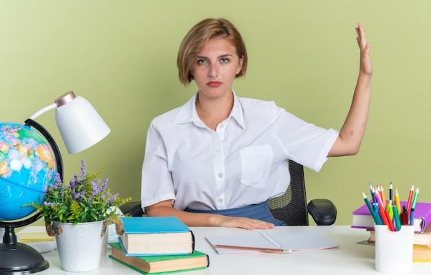 Grave giovane studentessa bionda seduta alla scrivania con gli strumenti della scuola guardando la telecamera facendo il gesto di arresto a lato isolato su parete verde oliva