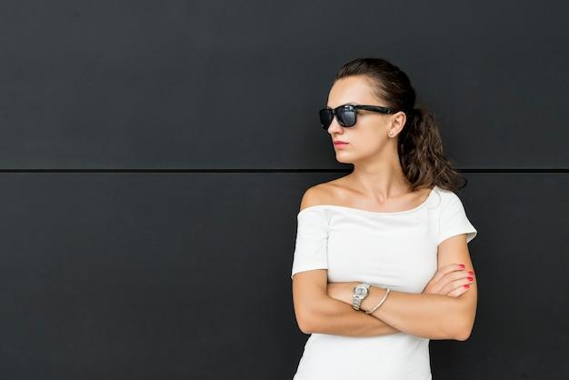Grave giovane donna bruna in camicia bianca in piedi con le braccia incrociate su sfondo nero
