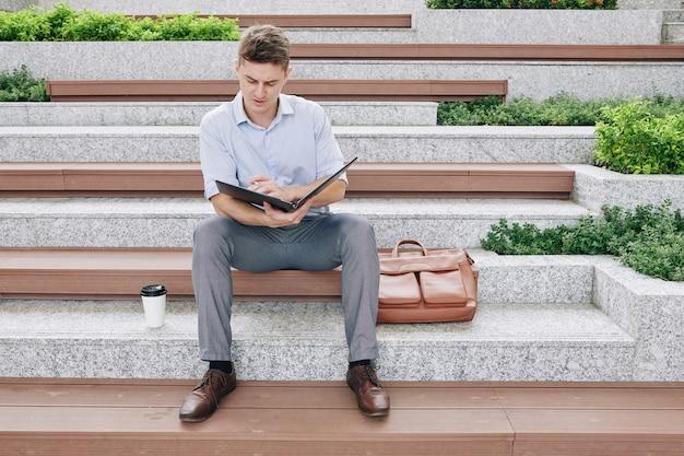 Grave giovane imprenditore leggendo i documenti nella cartella, controllando la relazione finanziaria e apportando correzioni