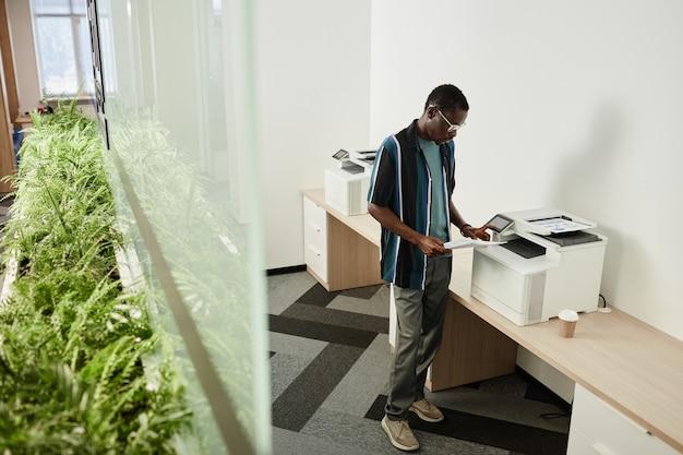 Un giovane uomo d'affari serio che sta alla fotocopiatrice e controlla i rapporti che ha stampato per l'incontro