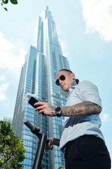 Grave giovane uomo d'affari in piedi su scooter davanti al grattacielo e leggere il messaggio di testo sullo smartphone
