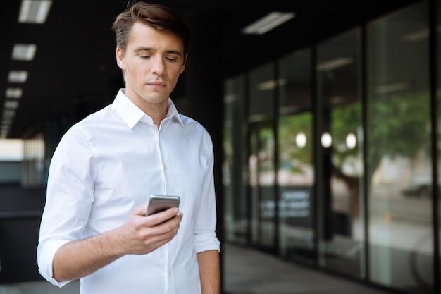 Grave giovane imprenditore in piedi e utilizza lo smartphone