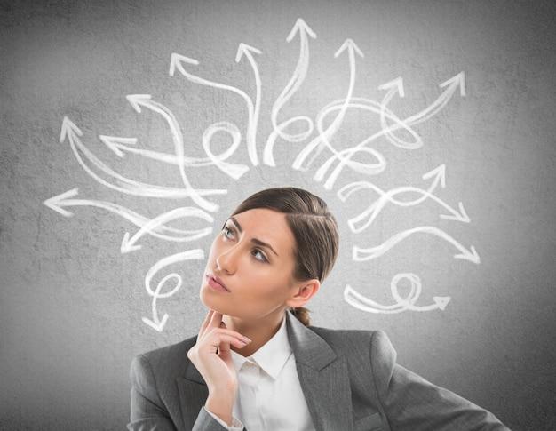 Donna di affari seria e giovane che esamina molte frecce torte sul muro di cemento ambientale