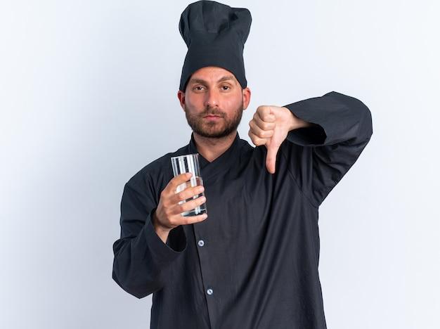 Serio giovane maschio caucasico cuoco in uniforme da chef e berretto con in mano un bicchiere d'acqua che mostra il pollice verso il basso