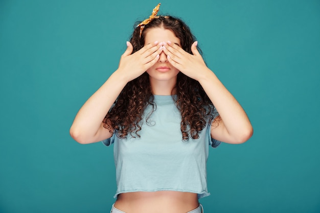 Grave giovane donna dai capelli ricci con sciarpa per capelli che copre gli occhi con le mani mentre gioca a nascondino