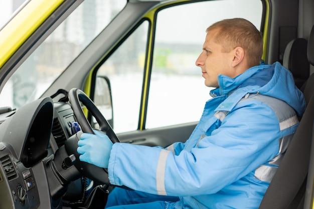 Grave giovane conducente di auto ambulanza seduto da sterzare mentre aspetta i paramedici che salvano persona malata all'aperto