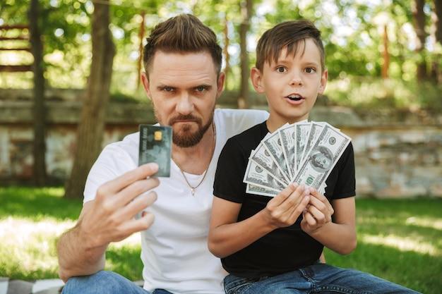 Giovane padre serio che si siede con il suo piccolo figlio che tiene soldi e carta di credito.
