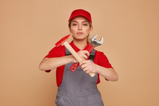 Grave giovane operaio edile femminile che indossa il cappello e uniforme tenendo la chiave e il martello che non fanno alcun gesto
