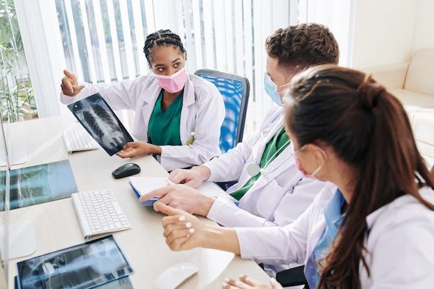 Grave giovane dottoressa in maschera medica che mostra ai colleghi i raggi x dei polmoni del paziente con sospetto coronavirus