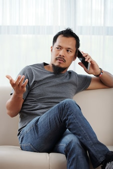 Giovane serio che gesticola attivamente quando è seduto sul divano in soggiorno e parla al telefono