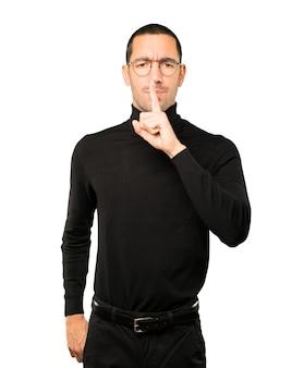 Giovane serio che chiede silenzio gesticolando con il dito