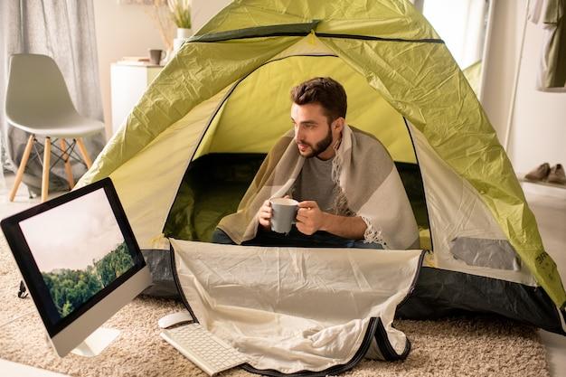 Giovane serio sotto la coperta che si siede con la tazza in tenda da campeggio e guardando la foto della foresta sul monitor in soggiorno, concetto di isolamento