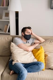 Giovane serio in depressione che indossa la maschera di stoffa appoggiato la testa a portata di mano mentre è seduto sul divano durante la quarantena
