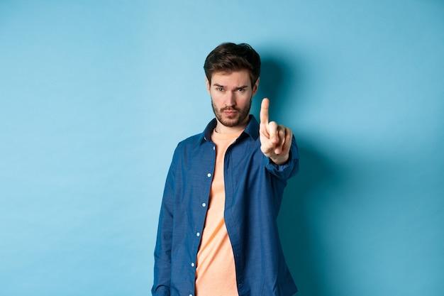 Il giovane serio allunga un dito per fermarti o avvertirti, proibire qualcosa o disapprovare, in piedi su sfondo blu. copia spazio