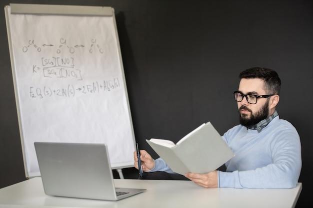 Giovane serio in occhiali e libro di lettura di abbigliamento casual mentre era seduto davanti al computer portatile durante la lezione online di chimica a casa