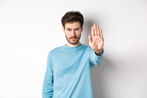 Giovane serio che sembra fiducioso con la mano tesa, dicendo stop, proibire qualcosa di brutto o dare avvertimento, in piedi su sfondo bianco