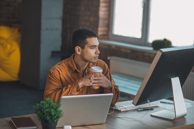 Giovane serio che guarda lo schermo del laptop mentre era seduto con una tazza di caffè