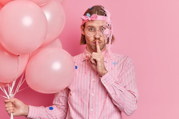 Il giovane serio fa il gesto di silenzio vestito con abiti festivi dice che le informazioni segrete godono delle pose di celebrazione della festa con palloncini isolati sopra il muro rosa