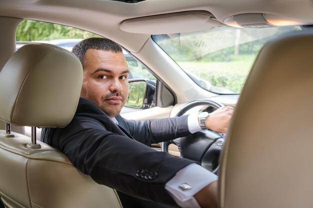 Giovane serio di aspetto mediorientale in giacca e cravatta al volante di un'auto costosa