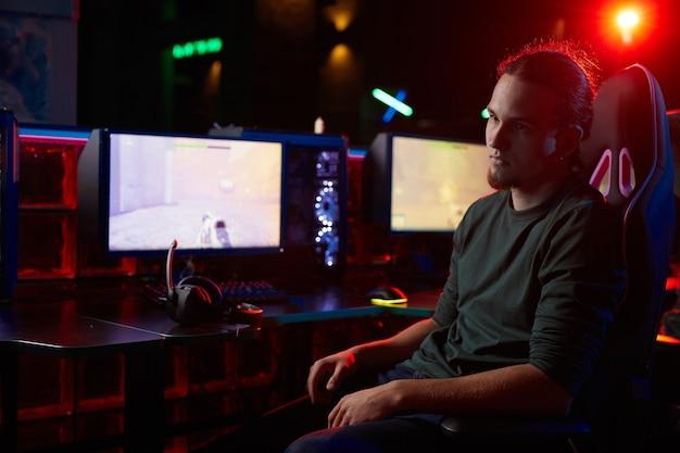 Giovane serio che si siede sulla sedia davanti ai computer con il gioco per computer che osserva via che riposa dopo il gioco