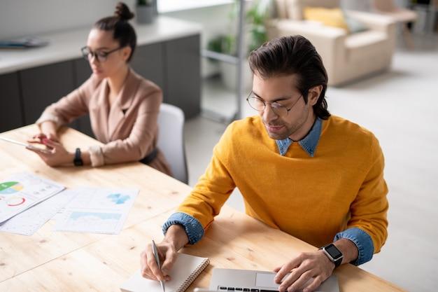 Grave giovane manager in occhiali da vista prendere appunti durante l'analisi dei dati del sito web sul portatile in ufficio