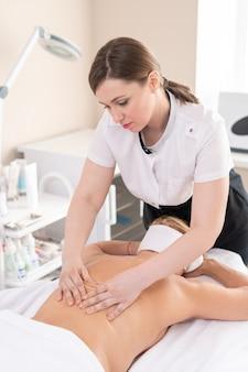 Grave giovane massaggiatore che fornisce il trattamento per la donna con la schiena nuda nel salone della stazione termale