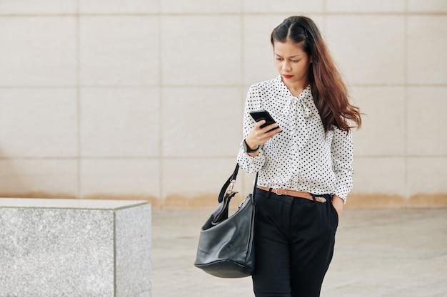 Grave giovane donna d'affari di razza mista che cammina all'aperto e controlla i messaggi di testo nel suo telefono