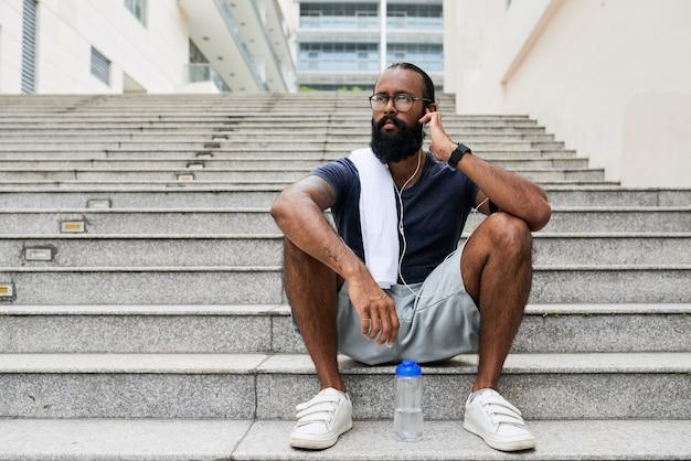 Grave giovane uomo di razza mista con la barba seduto sul gradino e guardando in lontananza mentre si regola l'erphone nell'orecchio