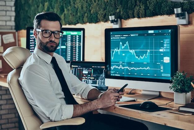 Serio giovane uomo moderno in abiti da cerimonia che usa lo smartphone e guarda la macchina fotografica mentre è seduto in ufficio