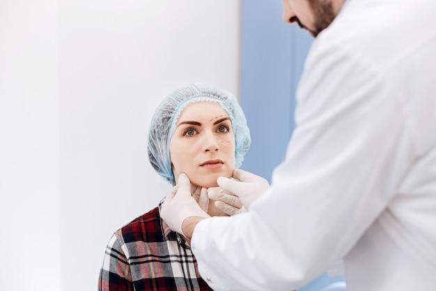 Grave giovane bella donna che indossa un berretto e seduto davanti al suo chirurgo plastico pur avendo un appuntamento con lui