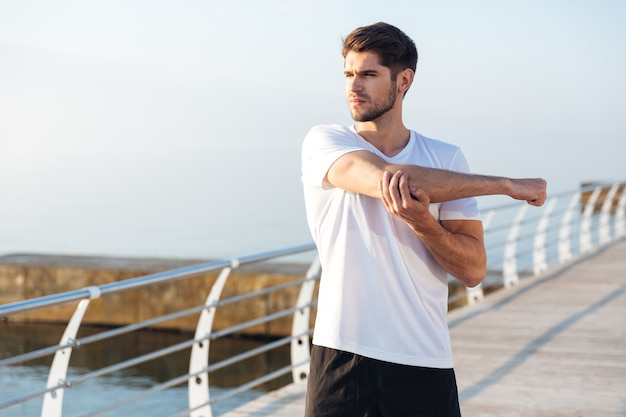 Giovane sportivo serio in piedi e allunga le braccia all'aperto al mattino