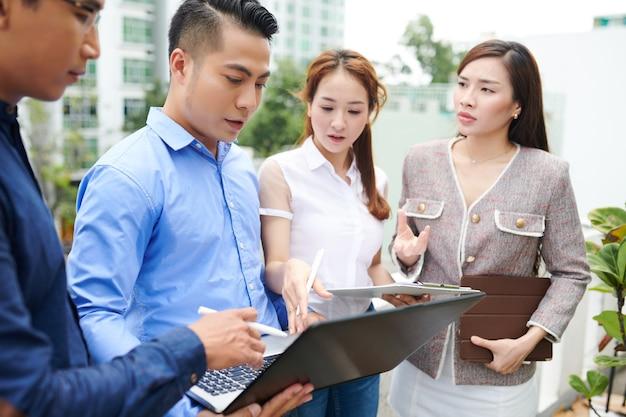 Gravi giovani imprenditori vietnamiti in piedi all'aperto e discutendo la presentazione del prodotto sullo schermo del laptop