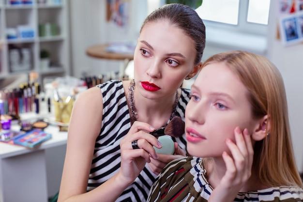 Giovane donna seria che applica polvere facciale sul viso mentre si trova vicino al suo cliente
