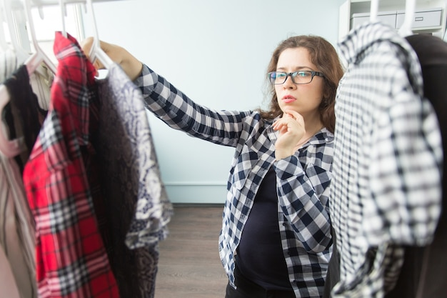 Grave giovane donna che sceglie i vestiti nel suo guardaroba.