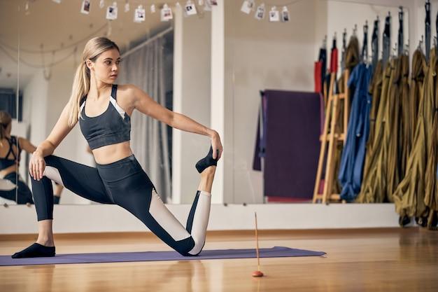 Giovane donna seria che fa esercizi di stretching sul tappetino da yoga mentre si tocca i piedi con la mano