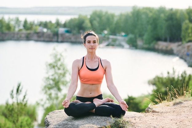 Giovane donna seria concentrata sulla mente seduta con le gambe incrociate sulla pietra alla cava e meditando da sola