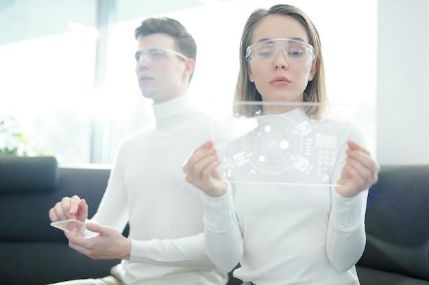 Grave giovane donna in occhiali intelligenti analizzando lo schema sul dispositivo vetroso mentre il suo fidanzato utilizzando il pannello di controllo trasparente