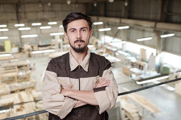 Grave giovane operaio in uniforme con le braccia incrociate dal petto in piedi contro l'interno della grande officina della fabbrica