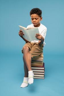 Grave scolaro giovanile in abbigliamento casual e calzini bianchi seduto in cima a un'alta pila di libri e leggendo uno di essi
