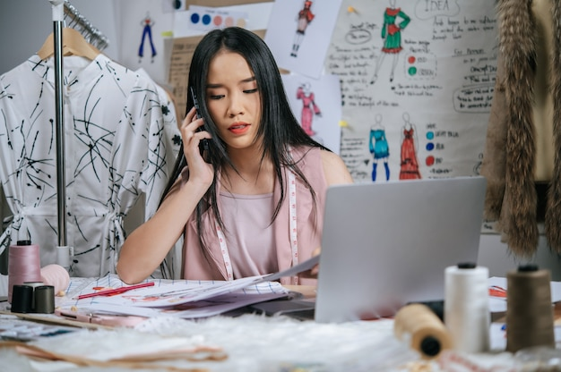 Seriamente il giovane designer che parla con lo smartphone mentre usa il computer portatile per controllare insieme