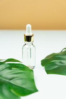 Bottiglia di siero vicino a foglia di palma. prodotto di bellezza alla moda per la pelle giovane. fase idratante aggiuntiva nella routine quotidiana del viso. copia spazio.