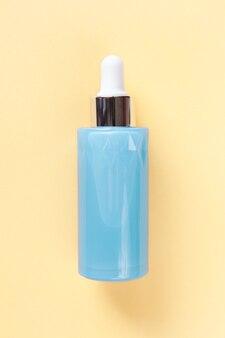 Siero per la pelle del viso o degli occhi in una bellissima bottiglia blu con contagocce giallo