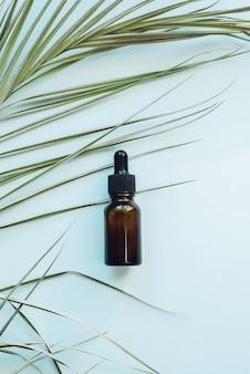 Siero per pelli con collagene e peptidi. bottiglie di vetro con contagocce sotto le foglie di palma