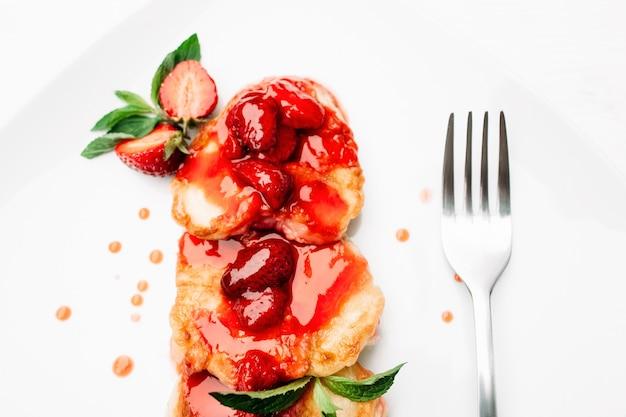 Dessert servito di frittelle e fragole