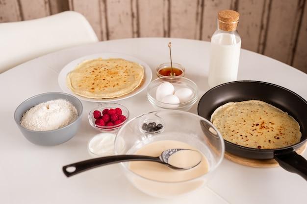 Tavolo da cucina servito con pancake caldo in padella, ciotola con pasta, uova fresche, farina, miele, bottiglia di latte, panna acida, lamponi e more