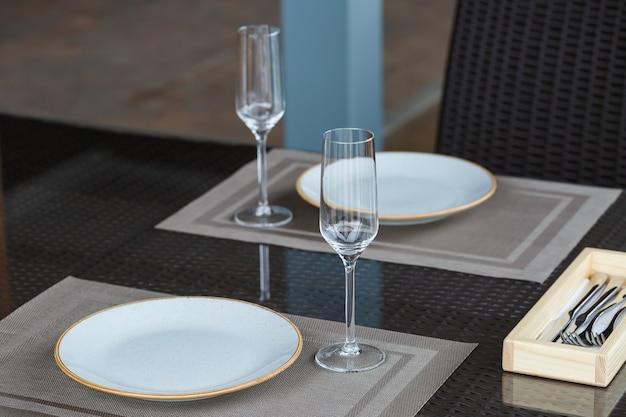 Tavola servita in un ristorante per due. piatti blu per il cibo, due bicchieri.