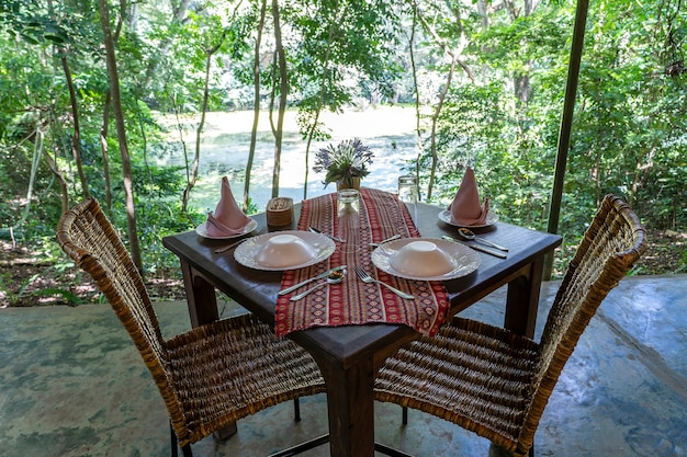 Tavolo servito e due sedie in rattan sulla terrazza di un ristorante vuoto. tanzania, africa orientale