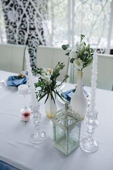 Servito per la tavola del banchetto di nozze in bianco blu. decorazione di nozze. tovagliolo blu con fiore su un piatto bianco. arco traforato.