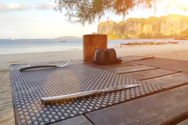 Tavola di legno servita su una spiaggia tropicale preparata per la colazione vicino al mare
